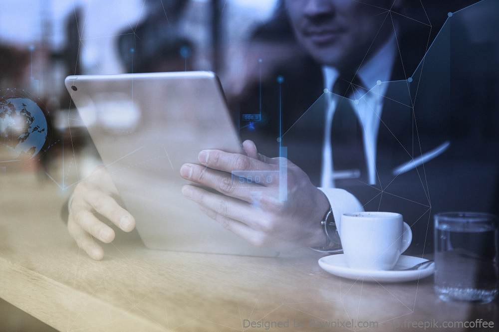 Businessman working on tablet in cafe