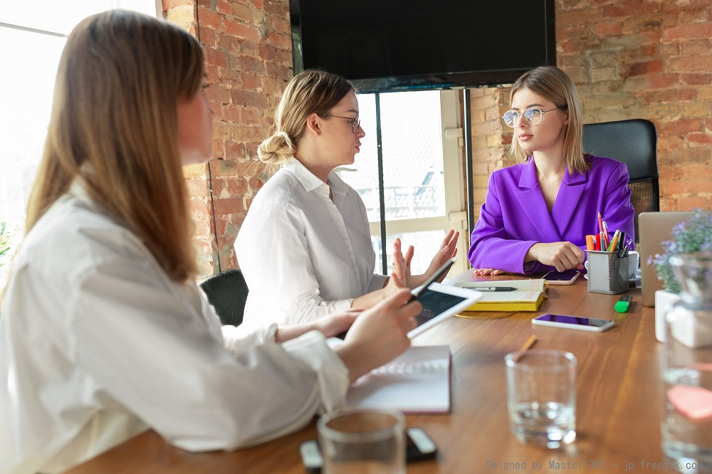 Leader. Young caucasian business woman in modern office with team. Meeting, tasks giving. Women in front-office working. Concept of finance, business, girl power, inclusion, diversity, feminism.